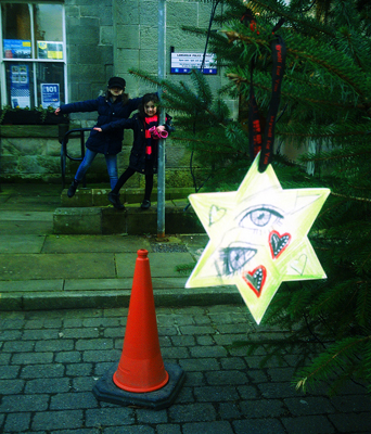 """14. Dec – Lucy MacLeod, Langholm  """"I decided to decorate the star with pencil and charcoal drawings of both of my daughters' eyes. Both Maisie (aged 8) and Rose (aged 5) will be 90 miles away in Fife with their Dad on Christmas day this year and as I most enjoy Christmas vicariously through their excited eyes, by having this decorative reminder I like to think that a wee part of them will be here with me in Langholm. Myself and my girls hung the star on the 20ft tree at the far end of Langholm high street for the day and it miraculously clung on to it's branch despite turbulent conditions! We then brought it indoors to hang (hopefully annually!) on our own christmas tree."""""""